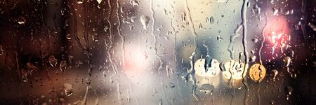 Panoramic image. Blurred car lights. Raindrops on the front window