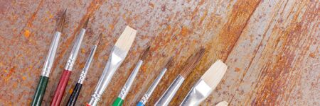 Row of colorful paint brushes are lying on the rusty background. Panoramic image