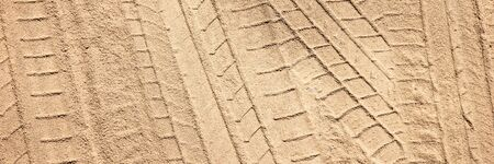 Panoramic image. Tire tracks on the sand. Sand texture
