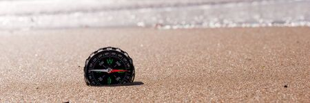 Compass in the sea sand at the beach, water in background. Panoramic image