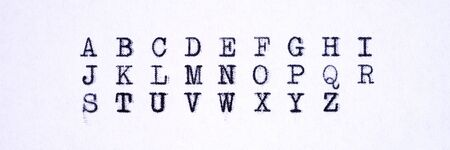 Panoramic image. Alphabet written with an old typewriter. Letters isolated on white paper sheet