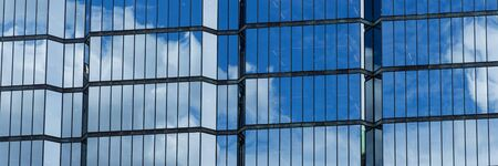 Panoramic image. Windows of a skyscraper with reflection of blue sky and white clouds 版權商用圖片