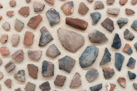 Different colorful small stones isolated on sandy background. Background of stones 版權商用圖片