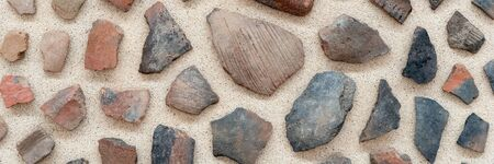 Different colorful small stones isolated on sandy background. Background of stones Banco de Imagens