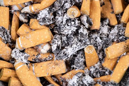 Many used cigarette butts and ashes. Background