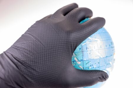 Hand with black rubber gloves holds the globe. Epidemic of coronavirus. The pandemic concept Stock Photo