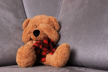 Teddy bear sits on the sofa and covers his eyes. Child abuse concept