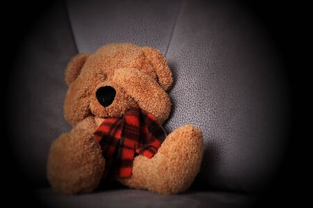 Child abuse concept. Teddy bear sits on the sofa and covers his eyes