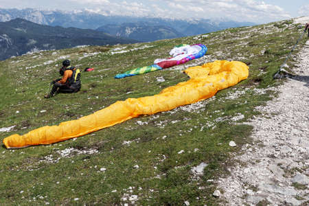 Woman is waiting for paragliding on the mountain. Krippenstein mountain in the Dachstein Mountains. Salzkammergut. Austria Stock Photo
