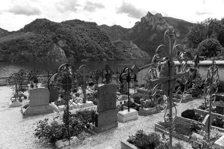 Black and white image. Cemetery with a view of the lake and the mountains