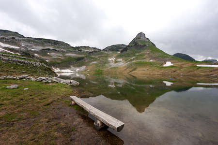 Lake in the austrian Alps with reflection from mountain in the water. Augstsee. Loser. Austria