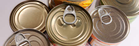 Various canned food in metal cans, top view. Panoramic image