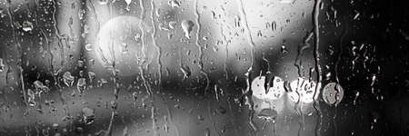 Panoramic image. Blurred car lights in black and white. Raindrops on the front window 免版税图像