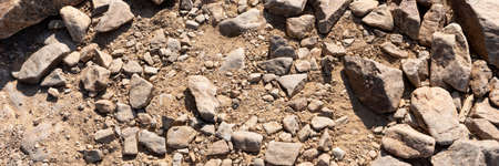 Panoramic image of the surface covered with big stones on the ground. The surface of the hiking trail. Top view 写真素材