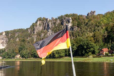 Waving National Flag of Germany and mountains in Saxon Switzerland. Germany