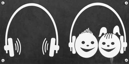 Headphones as a sign for audio guide and audio guide for children on black background 版權商用圖片