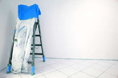 Wooden ladder with painter pants and blue T-Shirt in a room