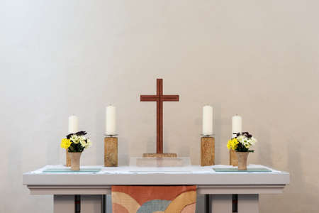 Altar with a wooden cross and four candles against a light background