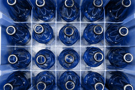 Empty blue glass beer bottles in the plastic box