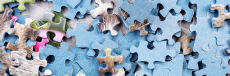Panoramic image of jigsaw puzzle pieces. Many pieces of an unfinished puzzle