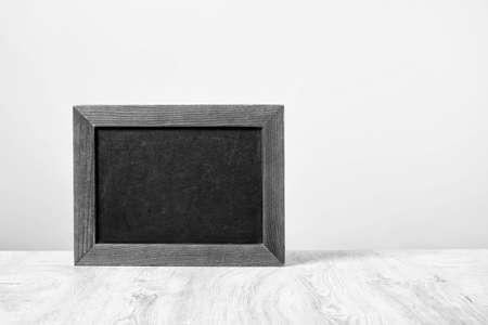 Empty black chalkboard isolated in front of a white wall Stock Photo