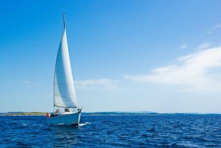 Sailing boat on blue sea photo