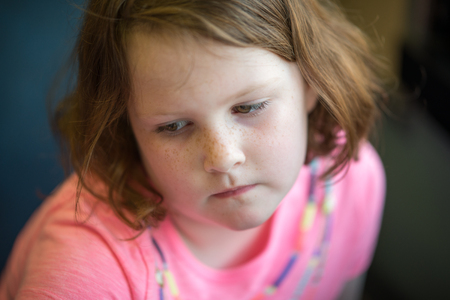 huffy: Close Portrait of Girl Thinking Sitting Down