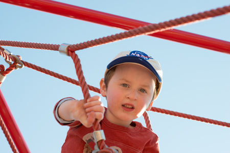 Young boy child playing at outdoor playground climbing net