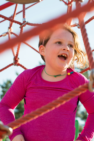 Young girl child playing at outdoor playground climbing net
