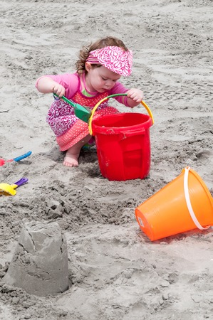 Young little girl playing with the sand and building sandcastle at the beach near the sea.