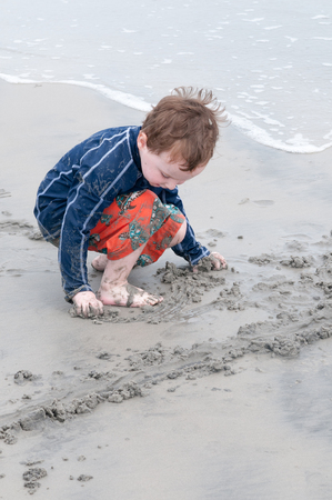 Young little boy playing with the sand and building sandcastle at the beach near the sea.