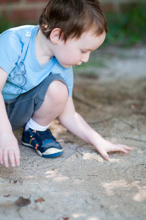 Adorable little boy playing in a sandbox Stock Photo