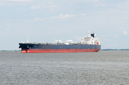 DELAWARE CITY, DE - AUGUST 1: Oil tanker ship coming into port on Delware river on a background of blue sky on August 1, 2015