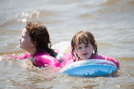 two young girls floating in inner tubes in a blissful state