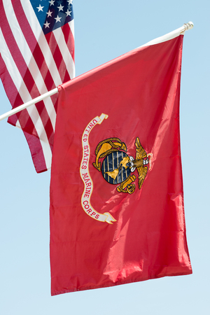 青空背景に手を振る米国海兵隊の旗を背景にアメリカの国旗でクローズ アップ、