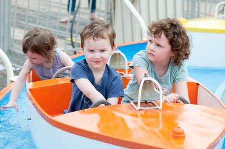 Young toddler sibblings having fun on boardwalk amusement ride