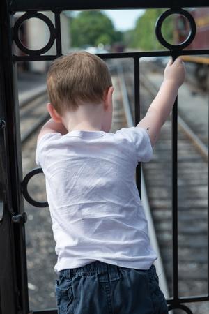 鉄道トラックを見て裏に立っている少年