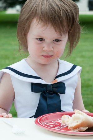 Young girl in fancy dress outside eating