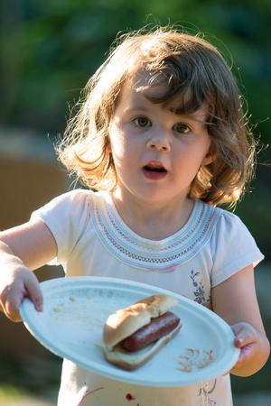 Cute toddler girl eating hot dog hotdog
