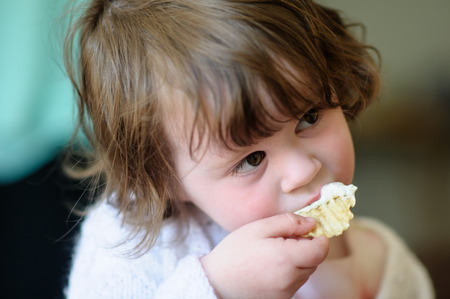 Portrait of a cute little girl inside eating potato chip with sour cream dip on it
