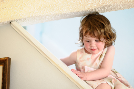 Portrait of a cute little girl inside on stairs Stock Photo