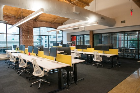 Trendy modern open concept loft office space with big windows, natural light and a layout to encourage collaboration, creativity and innovation