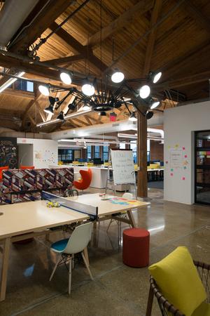 최신 창문, 자연 채광 및 협업, 독창성 및 혁신을 장려하는 레이아웃이있는 트렌디 한 현대 개방 개념 로프트 사무실 공간 스톡 콘텐츠