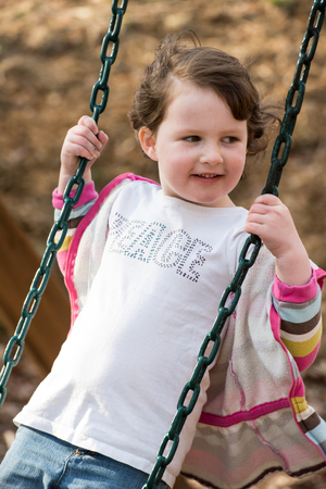 Young girl having fun outside at park on a playground swing set
