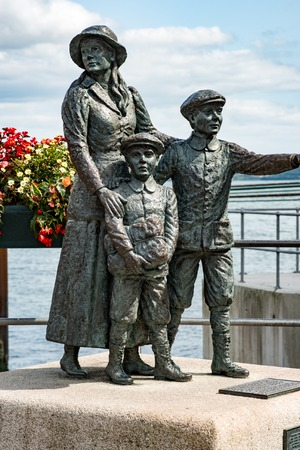 annie: The Annie Moore Memorial, statue of Annie Moore and her two Brothers in Cobh, Ireland Annie was the first immigrant to the United States to pass through the Ellis Island facility in New York Harbor Stock Photo