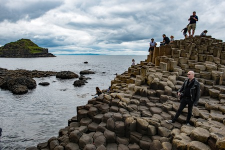 COUNTY ANTRIM, NORTHERN IRELAND - AUGUST 27, 2017: Group of tourists exploring the Giants Causeway
