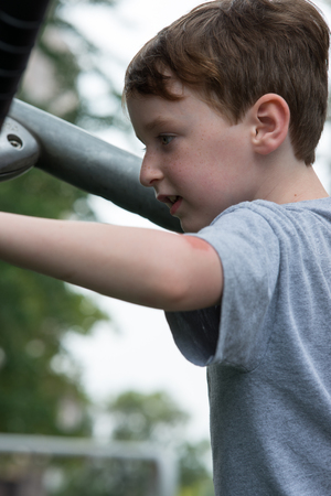 Young boy having fun outside at park on a playground climbing set