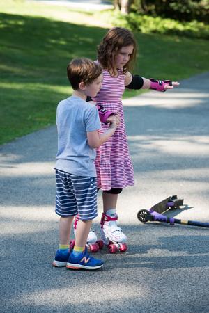 Chica joven fuera aprendiendo a montar en patines en la entrada usando codo protector, muñecas y rodilleras. Foto de archivo