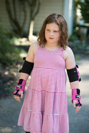 Chica joven fuera aprendiendo a montar en patines en la entrada con codo de protección, muñecas y rodilleras. Foto de archivo
