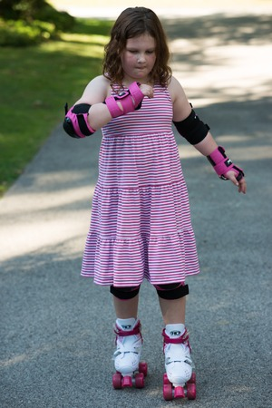 Young girl outside learning to riding on roller skates on driveway wearing protective elbow, wrist and knee pads Stock Photo